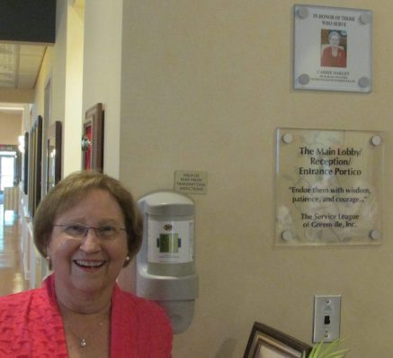 Sara Oakley Cozart next to plaque honoring her Mother, Carrie Oakley