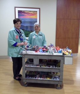SLG members Betty LeRoux and Ann Coker pushing the snack cart through the Cancer Center